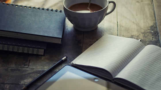 Journals, coffee and tablet on wooden table