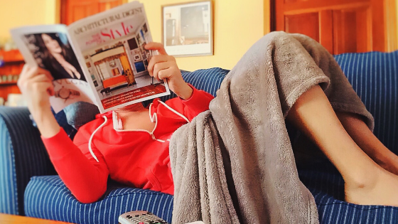 Woman laying on couch reading a magazine.