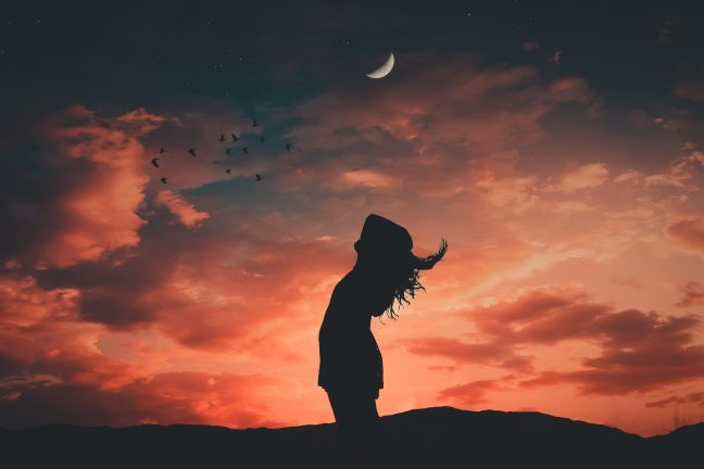 Woman's silhouette under waning moon