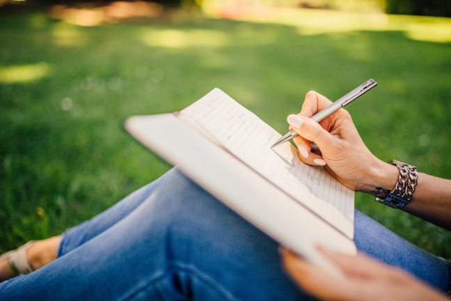 woman sitting in grass writing in a journal